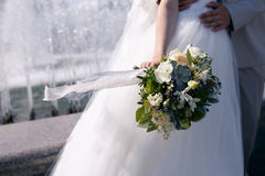 Green and white wedding bouquet in hands of the bride with a fluttering in the wind blue lace ribbon. On a background of a fountain Stock Images