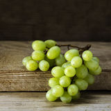 Green white wine grapes lying on rustic wood, dark background Stock Photography