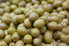 Green whole olives in oil close up. Green whole Italian olives in oil close up background, retail market stall display Royalty Free Stock Images