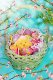 Green wicker basket with easter eggs and chicken Stock Photo