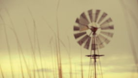 Green wind energy: vintage running farm windmill at sunset stock video