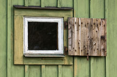 Green Window. A small window with shutter on a green wall royalty free stock image