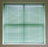 Green Window Blinds. Large square window covered with green blinds Royalty Free Stock Images