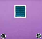 Green window and cooling fan on purple wall. For background Royalty Free Stock Image