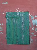 Green window on a red and grunge wall texture Royalty Free Stock Photography
