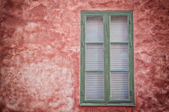 Green window on red wall. Stock Photo