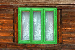 Green window of a rustic old house with wooden walls. The window of the old rustic house on the background of wooden walls Stock Images