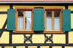 Green window shutters of a yellow house. With brown windows Royalty Free Stock Image