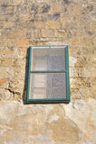 Green window in a stone wall in one of the old streets in Mdina, historic Malta capital.  Stock Images