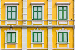 Green window on yellow wall Royalty Free Stock Image