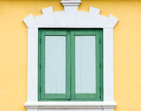 Green window on yellow wall. Royalty Free Stock Photos