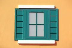 Green window with yellow wall Royalty Free Stock Image