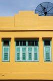 Green window on a yellow wall Stock Photo
