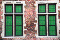Green Windows. A closeup of two green windows on a brick building stock images