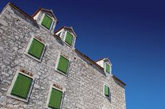 Old house with green windows on stone built facade. Green windows on the facade of stone house against blue sky Stock Photos