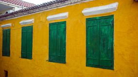Green windows. On the yellow facade stock photography