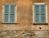 Green windows and orange wall. Old windows with blue or green shutters in an Italian city of Bergamo, Lombardy Royalty Free Stock Photo