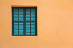 Green windows on orange wall Royalty Free Stock Photography