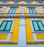Green windows with yellow wall Royalty Free Stock Photos