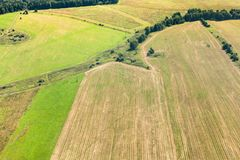 Green winter and yellow harvested fields on hills Stock Images