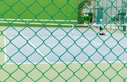 Green Wire Fence with Tennis Court Background Royalty Free Stock Photography