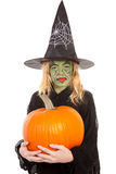 Green witch for halloween holding pumpkin Royalty Free Stock Image