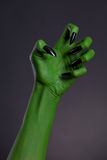 Green witch hand with sharp black nails, real body-art Stock Photography