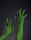 Green witch hands with black nails stretching up, real body-art Stock Photography