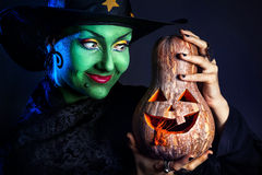 Green witch with pumpkin royalty free stock photography