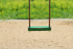 Green woioden swing on chain on playground at summer day Royalty Free Stock Photography