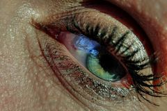 Green woman eye with black eyelashes. Green 40 years old woman eye with black eyelashes. There is visible red capilary on white of the eye royalty free stock images