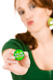Green: Woman Holding Out Kiss Me Pin. St. Patrick's Day holiday series with pretty girl in green outfit with various props Stock Photo