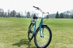 Green women`s bike with small white backpack on its trunk stays on green grass, early spring stock photos
