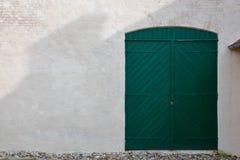 Green wood barn door in brick wall Stock Images