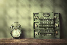 green wood calendar vintage and alarm clock on wood table end of Royalty Free Stock Photos