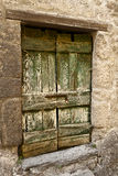 Green Wood Cellar Door. A rough-hewn and weathered cellar door in the hill town of Civita in Umbria, Italy. The green paint on the wooden door is peeling and Royalty Free Stock Images