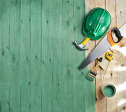 Green wood floor with a brush, paint, tools and helmet Stock Photo
