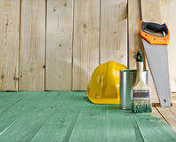 Green wood floor with a brush, saw and helmet Stock Images