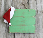 Green wood sign with Christmas Santa Claus hat hanging on aged wooden background Stock Photos