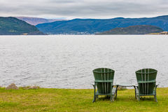 Relaxing in Gros Morne coastal landscape NL Canada. Green wooden Adirondack Chairs in beautiful coastal landscape of Gros Morne National Park, Newfoundland, NL stock photography