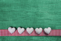 Green wooden background with hearts on a red white checked frame Stock Images
