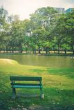 Green wooden bench in public park with lake and trees background.Park in city and sky background.Summer with nature. Landscape royalty free stock images