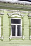 Green wooden countryhouse, facade and window. Icicles cover the roof. Color winter photo taken in Russia Royalty Free Stock Photos