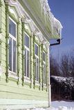 Green wooden countryhouse, facade and window. Icicles cover the roof. Color winter photo taken in Russia Stock Photos