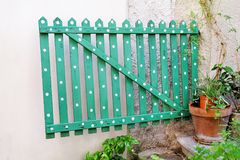 Green wooden decorative fence with floral flower elements and details / Part of the garden. Green wooden decorative fence with floral flower elements and Stock Image