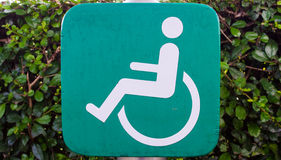 Green wooden disability sign Stock Photo