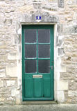 Green wooden door on a brick wall. A green wooden door in France Royalty Free Stock Image