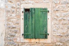 Green wooden door on brick wall Stock Photo