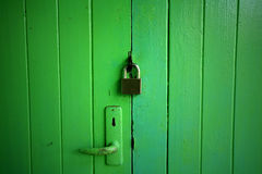 Green wooden door locked by master key Stock Photography