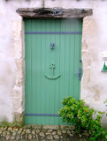 Green wooden door in a seaside village. Royalty Free Stock Photo